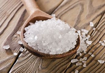 Salt in a spoon on  wooden  background.