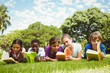 Children lying on grass and reading books - 79074774