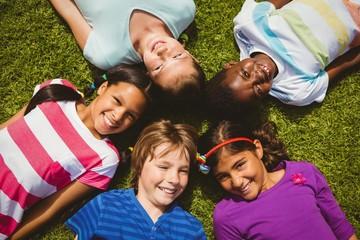 Portrait of children lying on grass at park