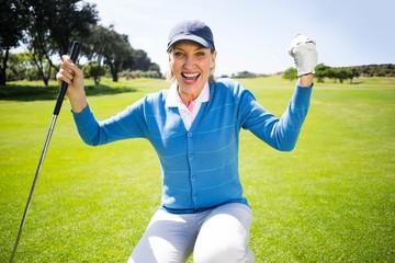 Kneeling lady golfer cheering on putting green