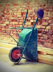 Wheelbarrow laid on the wall and worker's Cap