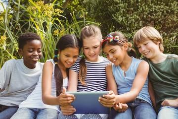 Children using digital tablet at park