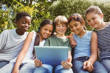 Happy children using digital tablet at park