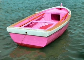 pink boat in the middle of the ocean