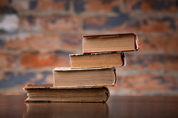 Vintage old books on a wooden table top  against a brick wall