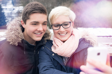 Young Girl and Boy making Selfie Outdoors