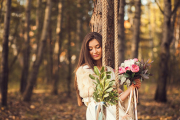 Portrait of romantic girl in the park with a bouquet of flowers
