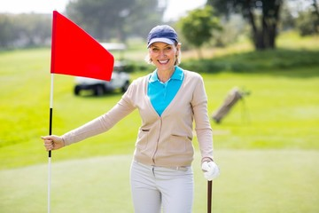 Female golfer smiling at camera and holding her golf club