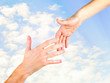 Woman's hand goes to the man's hand on sunny sky background