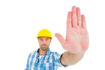 Confident manual worker gesturing stop sign