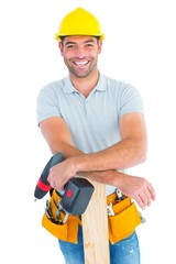 Smiling male carpenter with power drill and plank