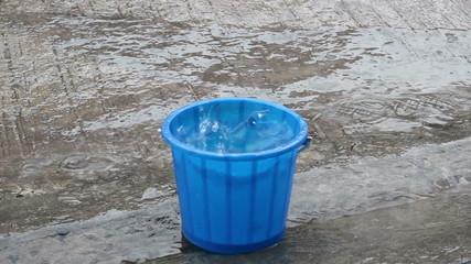bucket slave rain water flowing down