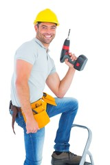 Confident handyman holding power drill while climbing ladder