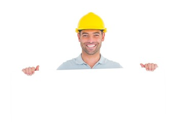 Happy handyman holding placard on white background