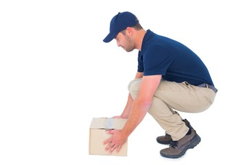 Delivery man crouching while picking cardboard box