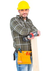 Carpenter holding power drill and wood plank