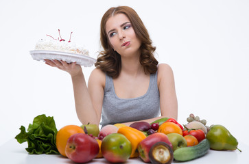 Woman sitting at the table with vegetables and holding cake