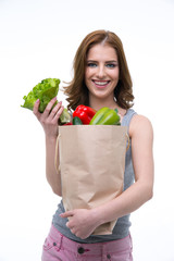 Smiling young woman holding a shopping bag full of groceries