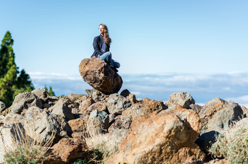 Young woman sitting on a rock in a beautiful place