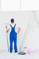 Handyman with paint roller examining wall at home