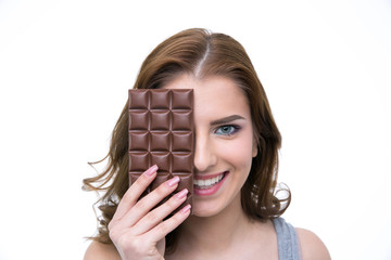 Smiling woman covering her eye with chocolate bar