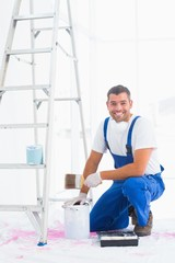 Smiling handyman with paintbrush and can at home