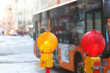 yellow and red lamps in roadworks in the city with a bus