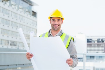 Happy architect holding blueprints outside building