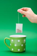 Hand putting a tea bag into