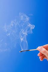 Hand holding burnt fuming matchstick