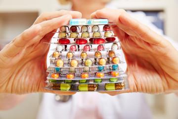 Hände vom Arzt halten viele Tabletten