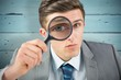 Composite image of businessman looking through magnifying glass - 79081191