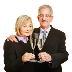 Paar Senioren stößt mit Glas Sekt an