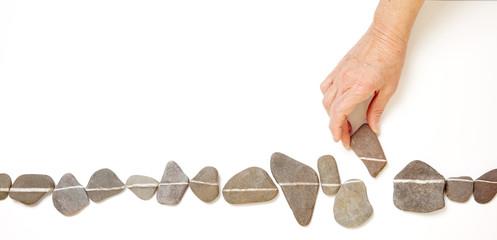 Alte Hand schiebt Stein in Linie