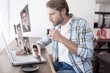Composite image of casual man using laptop drinking espresso