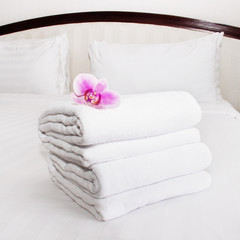 white towels and pink orchid on the bed