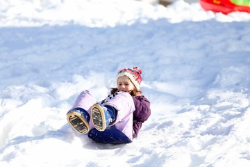 little girl plays with sledding on snow in the mountains