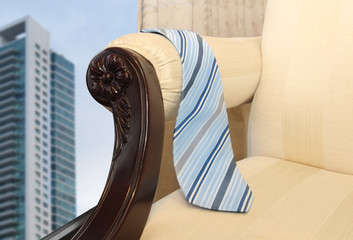 tie hanging on a chair facing the window