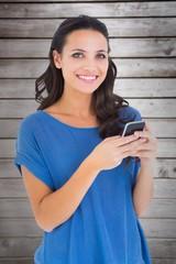 Composite image of pretty brunette sending a text