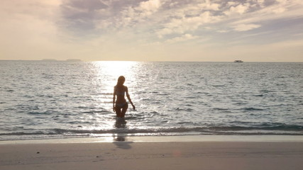 Silhouette of the woman leaving the sea at sunset