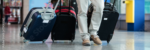 Leinwanddruck Bild mann mit koffern am flugplatz
