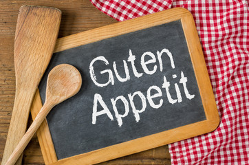 Tafel auf rustikalem Hintergrund - Guten Appetit