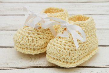 Pale Yellow Baby Booties on wood background