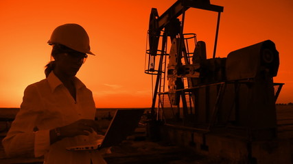Businesswoman with notebook working on oil field at sunset