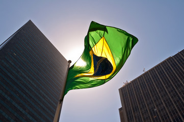 Brazilian National Flag against Skyscrapers by Sunset