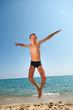 Boy jumps on the beach