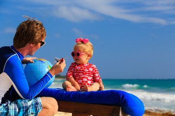 father and little daughter playing with globe on the beach