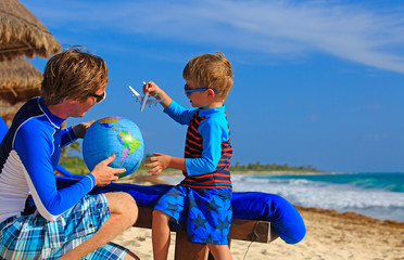 father and son playing with globe on the beach