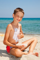 Boy applying sunscreen