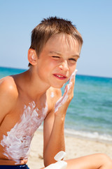 Boy applying sunscreen on face